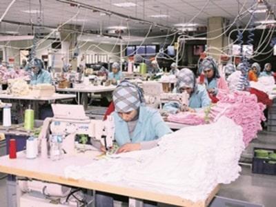 Fason dikim yapan atölye. Dikiş makinalarında tekstil ürünü diken sakin şekilde çalışıyor. Makinelerin üzerinde dikilecek kumaşlar var. Arka arkaya dizilmiş seri şekilde çalışıyorlar.