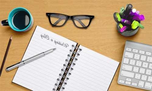 Masa üzerinde açık bir defter duruyor. Sağ tarafta klavyenin bir kısmı görünüyor. Defterin üst tarafında kalın çerçeveli gözlük var. Sol tarafta mavi renkli fincan ve önünde kurşun kırmızı kalem var. Aynı zamanda defterin üzerinde tükenmez kalem duruyor.