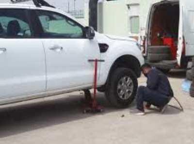 Beyaz renkli bir binek otomobil tamirciye getirilmiş. Kriko ile araç havaya kaldırılmış. Tamirci ise sağ ön tekerleği sökmeye çalışıyor. Üzerinde gri renk tulum var. Yere çömelmiş durumda.